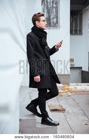 Full length business man in glasses and warm clothes with phone standing near the wall of house. Side view