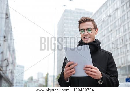 Business man with documents on the street. from below
