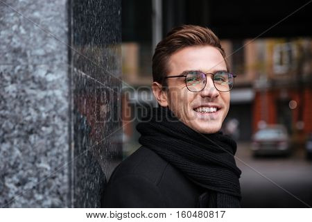Close up smiling business man in glasses and warm clothes near the building looking at camera