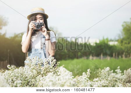 Outdoor summer smiling lifestyle portrait of pretty young woman having fun in the graden park with vintage camera travel photo of photographer Making pictures in hipster style. Relaxation and travel concept.