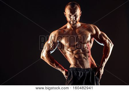 Strong bald bodybuilder with six pack. Strong bodybuilder man with perfect abs, shoulders, biceps, triceps and chest, personal fitness trainer flexing his muscles in blue, red smoke poster
