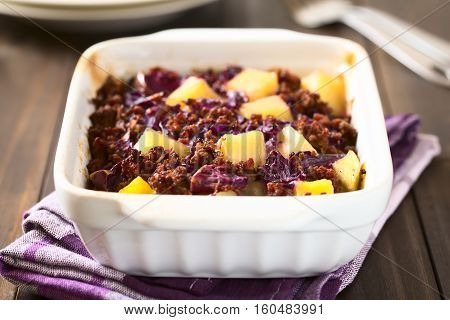 Baked red cabbage apple mincemeat and potato casserole in dish photographed with natural light (Selective Focus Focus one third into the dish)