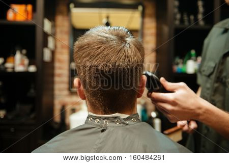 Picture of professional stylist cut hair of his client. Back view.