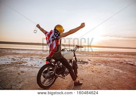 Young brutal man in golden helmet and american flag cape sitting on his motocycle with hands up in the air
