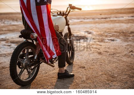 Cropped image of a brutal man wearing american flag cape sitting on his motocycle