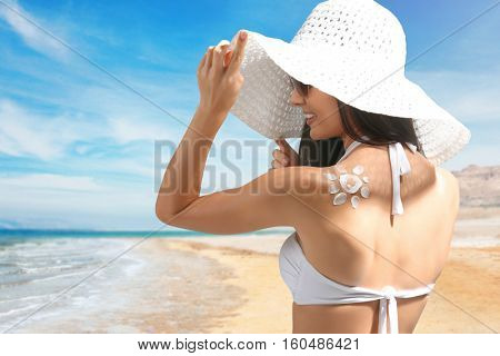 Woman with sun screen in sun shape on back. Skin care concept.