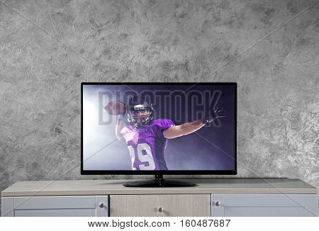Watching American football game on television at home. Leisure and entertainment concept.