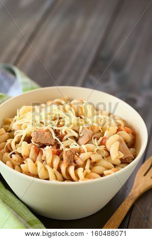 Rotini pasta with tuna and tomato sauce and grated cheese on top photographed with natural light (Selective Focus Focus in the middle of the dish)