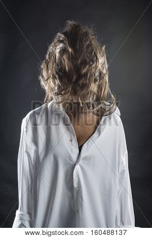 One woman with face covered of hairs over dark background