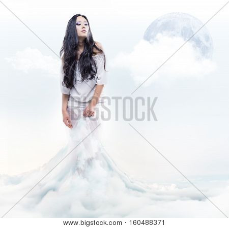 Young brunette girl white dressed on white clouds with moon in the sky