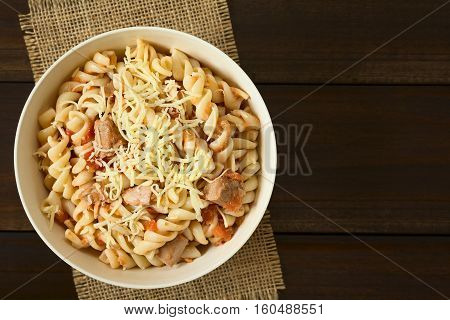 Rotini pasta with tuna and tomato sauce and grated cheese on top photographed overhead with natural light (Selective Focus Focus on the top of the dish)