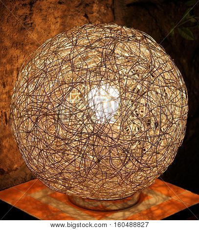 A modern lamp made from intertwined metallic wires.