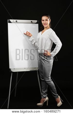 Young beautiful businesswoman with flip chart on black background