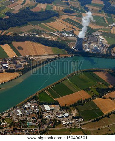nuclear power plant with a bird's-eye view. pollution of ecology against the background of cultivated fields near the river