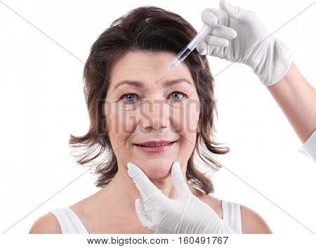 Senior woman having hyaluronic acid injection at beauty salon