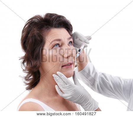 Senior woman having hyaluronic acid injection at beauty salon