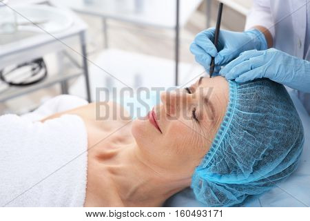 Surgeon hand drawing marks on female face for plastic operation