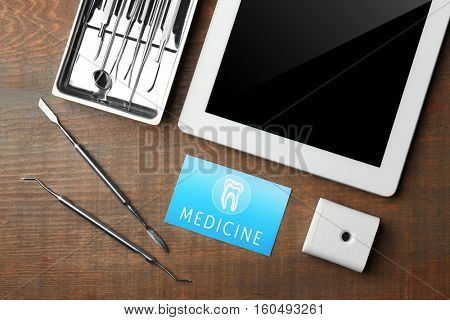 Business card, tablet and dental tools on wooden background. Medical service concept
