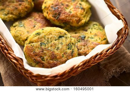Zucchini couscous and parsley fritters in basket photographed with natural light (Selective Focus Focus in the middle of the first fritter)
