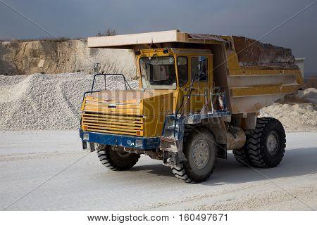 Moving dump truck full of chalk in quarry