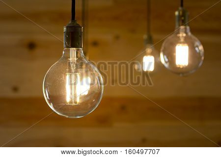 Group of filament light bulbs turned on over a wooden background.