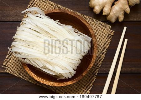 Raw rice flour noodles in wooden bowl photographed overhead on dark wood with natural light (Selective Focus Focus on the top of the noodles)