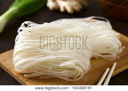 Raw rice flour noodles on wooden board photographed with natural light (Selective Focus Focus in the middle of the noodles)