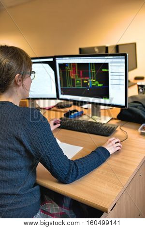 Young woman working in office on computer. Female architect in glasses designing building