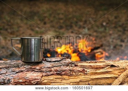 Iron cup with hot tea stands on a log near the fire. Journey into the wild concept.