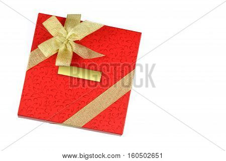 Red gift with blank label and decorated with gold ribbon isolated on a white background
