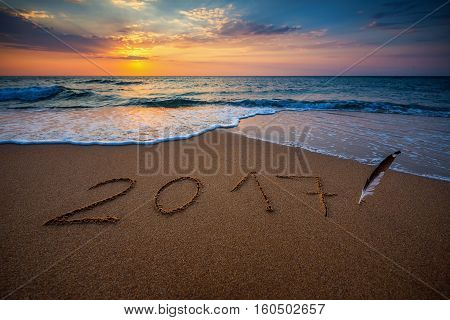 Happy New Year 2017 concept lettering on the beach