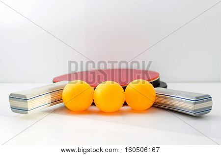 Rackets for ping pong and three yellow balls.