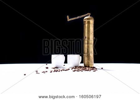 Coffee mill on the white table and two coffee cups and coffee seeds