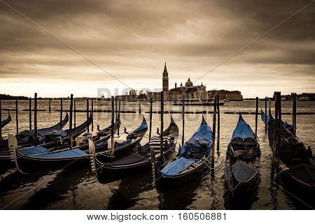 Gondolas in Venice in front of San Giorgio island Italy Europe Sepia filtered style