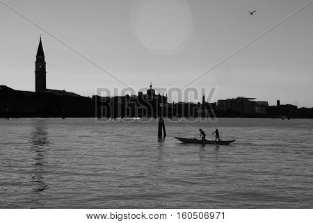 Venetian canal with a boat silhouette and San Giorgio di Maggiore church.