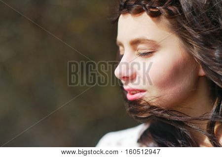 The portrait is cute beautiful long haired brunette girl with drooping lashes wind ruffling her silky curls closeup on blurred background