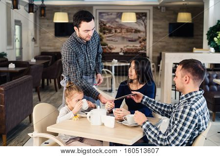 restaurant and holiday concept - waiter giving menu to happy family at restaurant.
