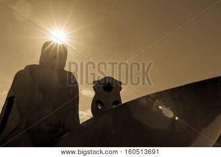 Lens flare sepia toned  chimneys and rooftop architecture Casa Mila a modernist building in Barcelona,