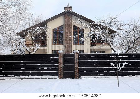 Front of suburban home under snow in winter