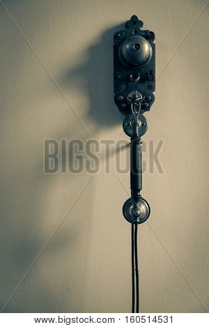 Old fashioned gritty image simple of telephone hanging on wall with shadow from side light
