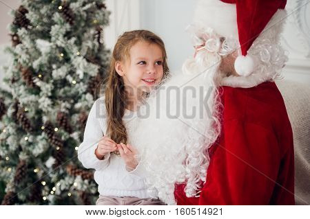 dream is real in christmastime. happy little cute girl sitting on the lap of aged Santa Claus and hugs at home near christmas tree.