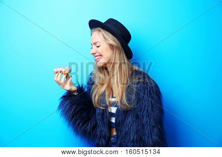 Young beautiful woman with doughnut on blue background