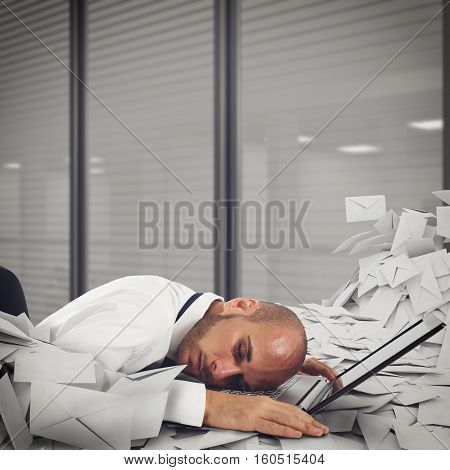 Businessman on laptop with a pile of worksheets and mail. Buried by work concept