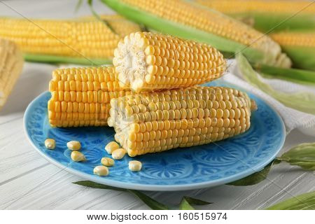 Plate with corncobs and seeds on wooden table