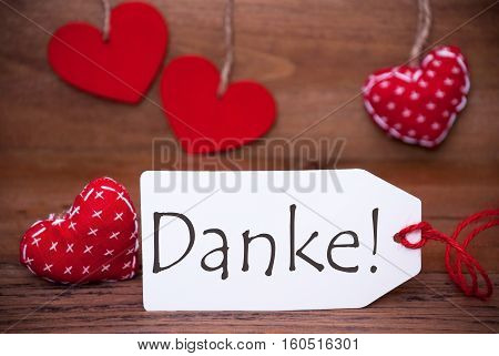 Label With German Text Danke Means Thank You. White Label With Red Textile Hearts. Retro Brown Wooden Background.