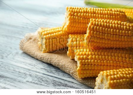 Corncobs with napkin on wooden white table
