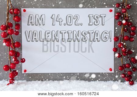 Label With German Text Am 14. Februar Ist Valentinstag Means February 14th Is Valentines Day. Red Decoration On Snow. Urban And Modern Cement Wall As Background With Snowflakes.