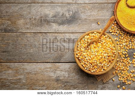 Corn seeds and groats in bowls on wooden table