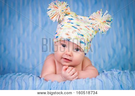 Newborn in a knitted cap on a blue background.