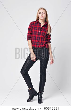 Flirtatious young blonde woman posing in red flannel shirt and black jeans. haughty look.